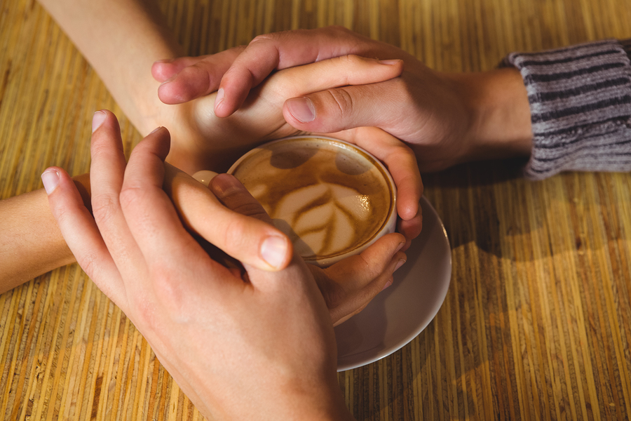 Couple holding hands around cappuccino with coffee art at coffee shop